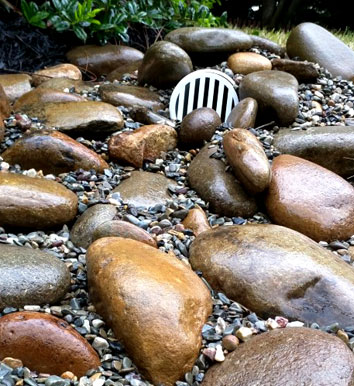 Creative Water Drainage Solution using River Rock and Pea Gravel